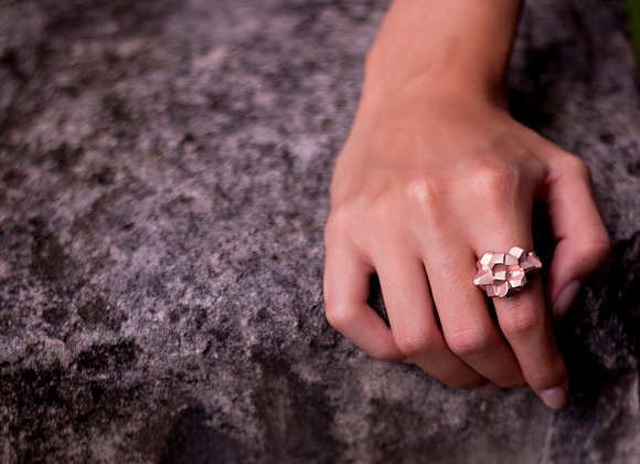 NUGGET x ROSE ring on woman's hand on rock